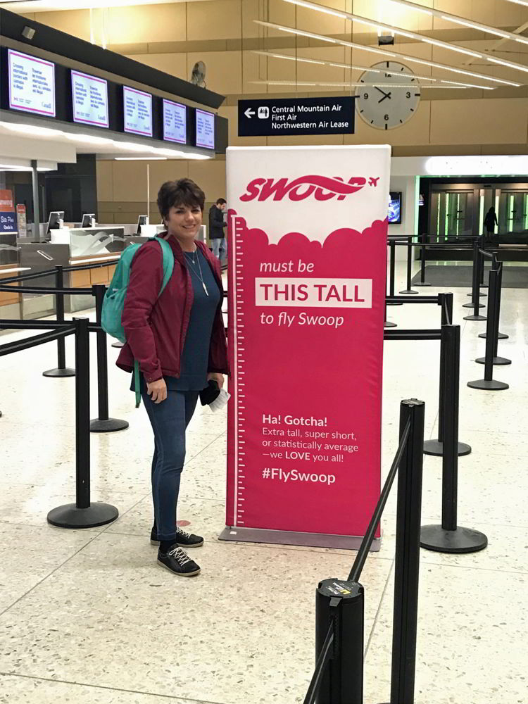 An image of a woman standing beside a Swoop Airlines sign - Swoop Airlines review