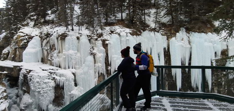 An image of a couple looking at ice formations in Johnston Canyon above the upper falls in Banff National Park, Alberta - Johnston Canyon Winter Hike and ink pots hike