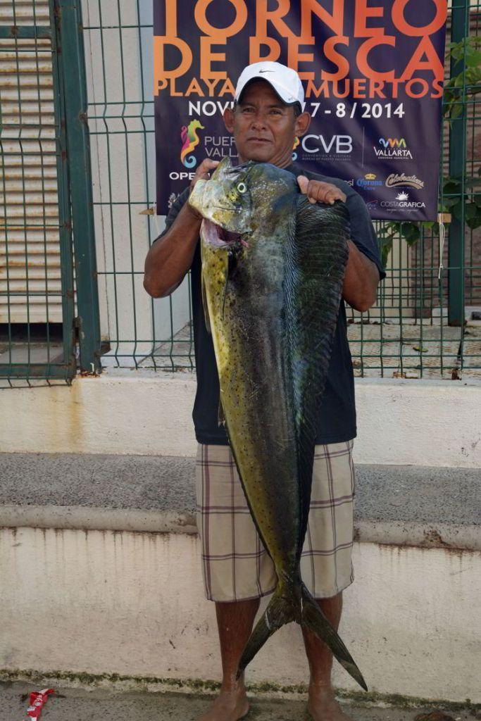 An image of a fisherman holding a fresh-caught mahi-mahi in Puerto Vallarta, Mexico - the best tacos in Puerto Vallarta