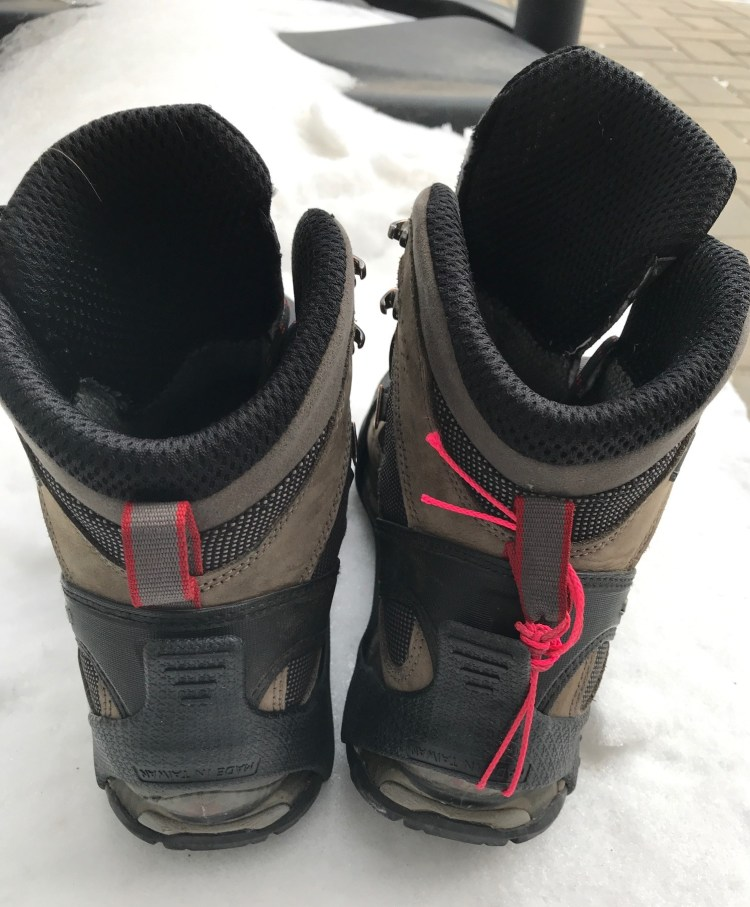 Image of left boot with GripOns applied normally and right boot with  a strap that we applied to secure the heel of the ice cleat on the boot. Microspikes for hiking review.