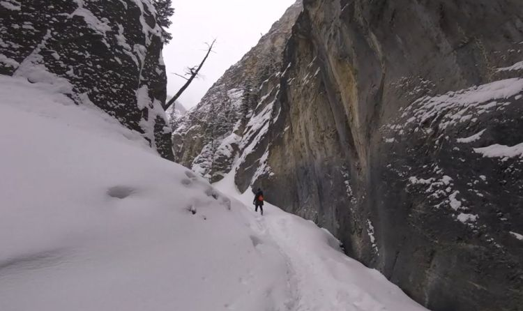 An image of a hiker walking through the frozen Grotto Canyon near Canmore, Alberta - Grotto Canyon Hike