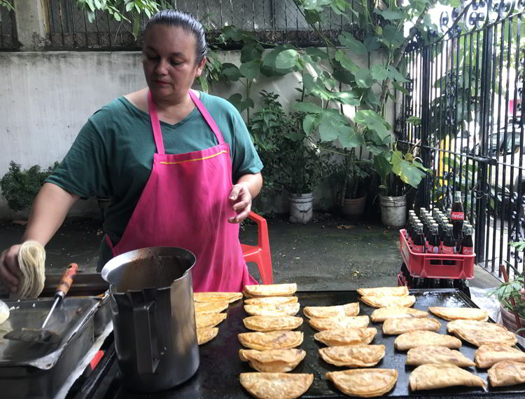 An image of a woman cooking fresh tortillas at Tacos Birria Chanfay in Puerto Vallarta, Mexico - the best tacos in Puerto Vallarta