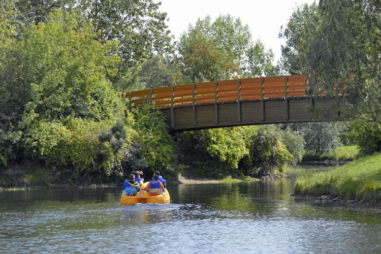 An image of two people in a peddle boat at Bower Ponds in Red Deer, Alberta, Canada.