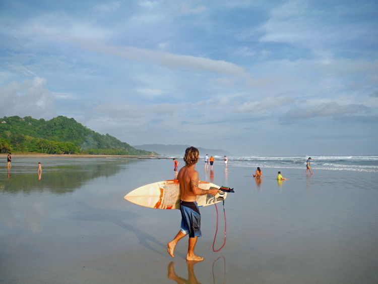 An image of a local carrying his surfboard to the beach to go surfing at Playa Hermosa in Costa Rica