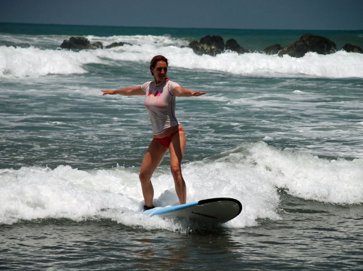 An image of a woman riding a wave at surf camp in Costa Rica.