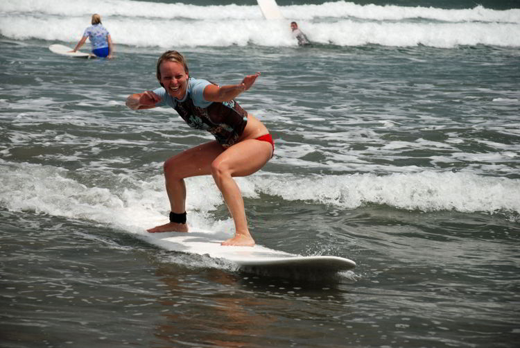 An image of a beginner surfer  riding a wave for the first time in Costa Rica.