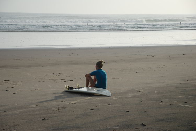 An image of a woman sitting on the beach with her surfboard in Costa Rica.