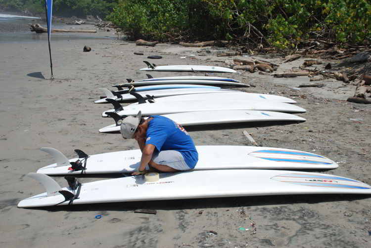 An image of a surf instructor preparing the boards at surf school in Costa Rica.