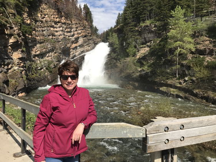 An image of a woman standing in front of Cameron Falls in Waterton Lakes National Park in Alberta Canada - Things to do in Waterton.