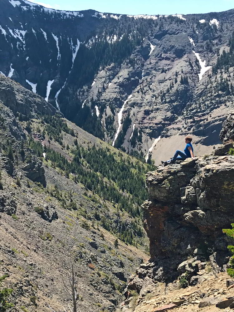 An image of a woman sitting on a rock outcropping partway up the Table Mountain hike in Alberta, Canada.
