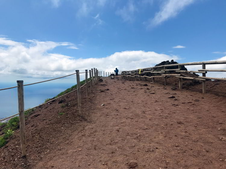 An image of the trail and a person hiking Mt Vesuvius in Naples, Italy.