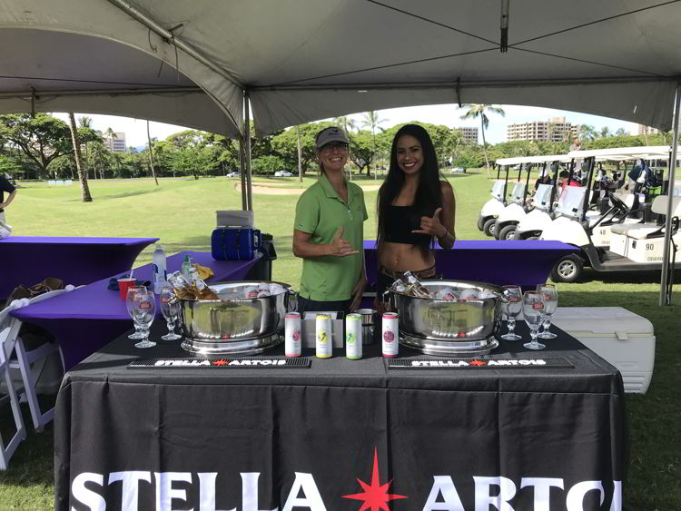 An image of two women handing out drinks at Roy's Golf Classic at the Hawaii Food and Wine Festival in Maui.