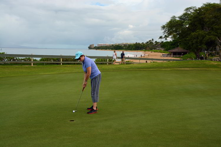 An image of a woman golfing at Kāʻanapali Golf Course.