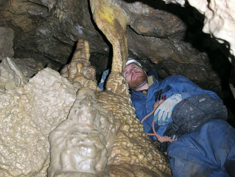 An image of a man looking at a rock formation inside the Rat's Nest Cave near Canmore, Alberta - Canmore Cave Tours