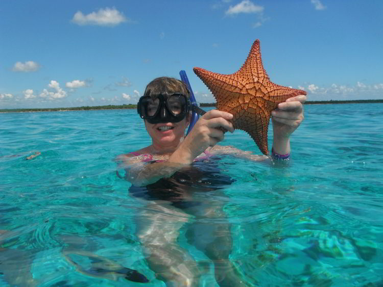 An image of a woman holding a starfish while snorkeling in Cozumel, Mexico - Riviera Maya excursions.