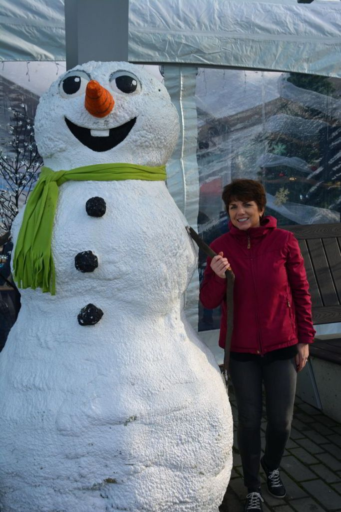 An image of a woman standing beside a snowman at the German Christmas Market in Vancouver, BC, Canada.