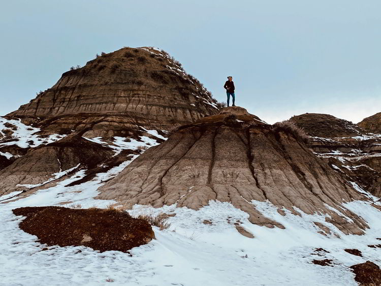 An image of a woman hiking in the badlands near Drumheller in the winter - Alberta road trips.