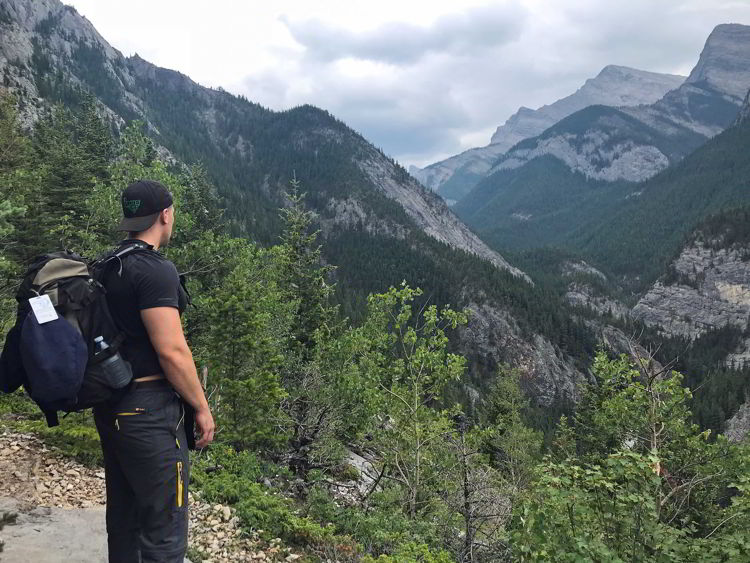 A picture of a young man taking in the view along the Heart Mountain hike near Canmore, Alberta.