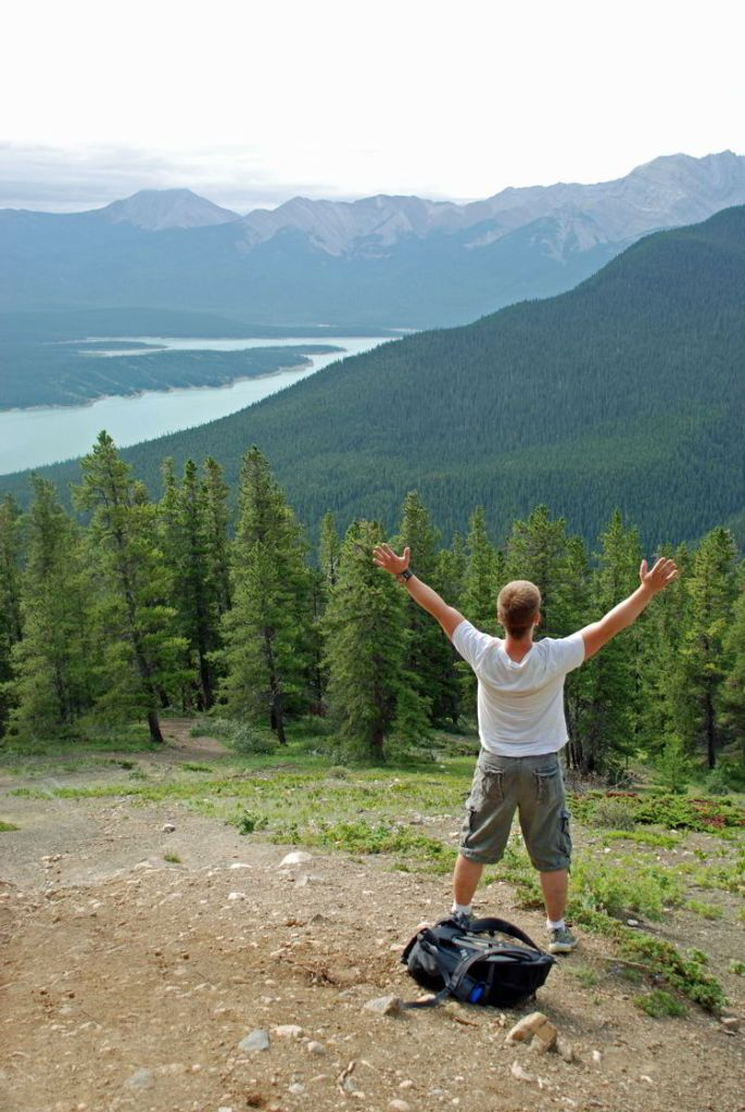 An image of a man with his arms up looking at the view along the Allstones Lake Trail in Bighorn Backcountry, Alberta, Canada.