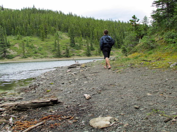 An image of a man walking around the shoreline of Allstones Lake in Alberta, Canada.
