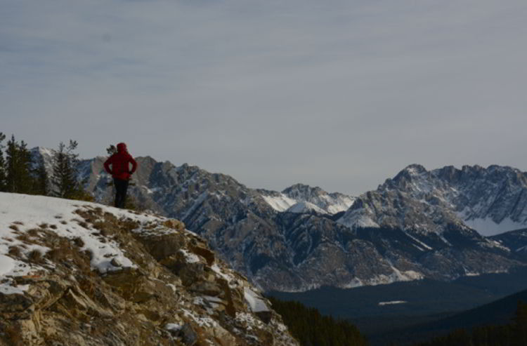 An image of a woman looking at the mountains in Kananaskis, Alberta Canada.