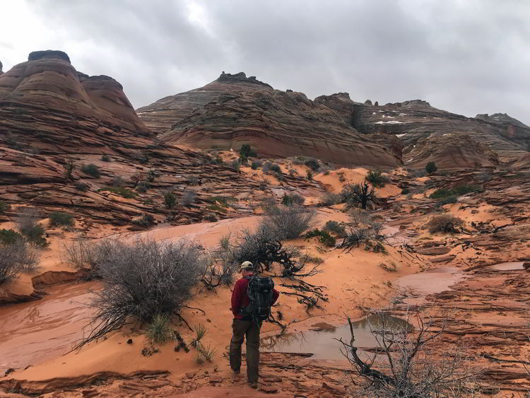 An image of a man hiking to The Wave in Arizona, USA.