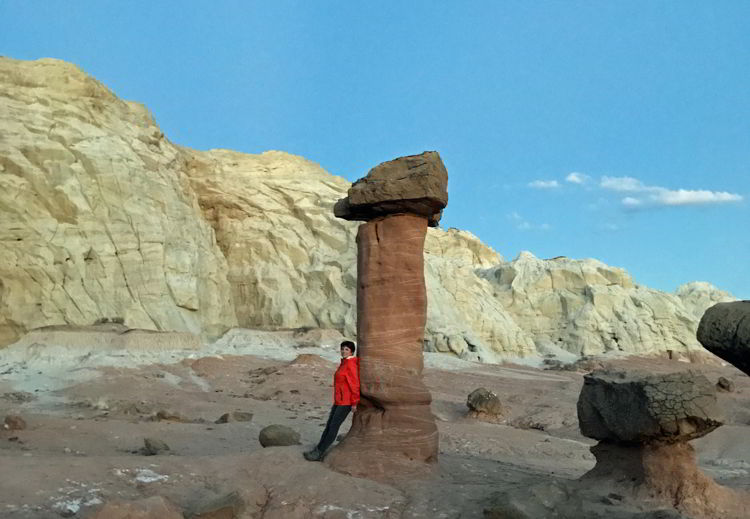 A photo of a woman standing next to one of the Toadstools in Grand Staircase-Escalante National Monument, Utah, USA