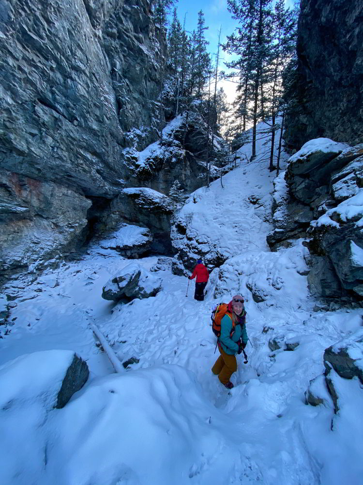 An image of two people hiking along the frozen creek on the Star Creek Falls ice walk in Crowsnest Pass, Alberta, Canada.