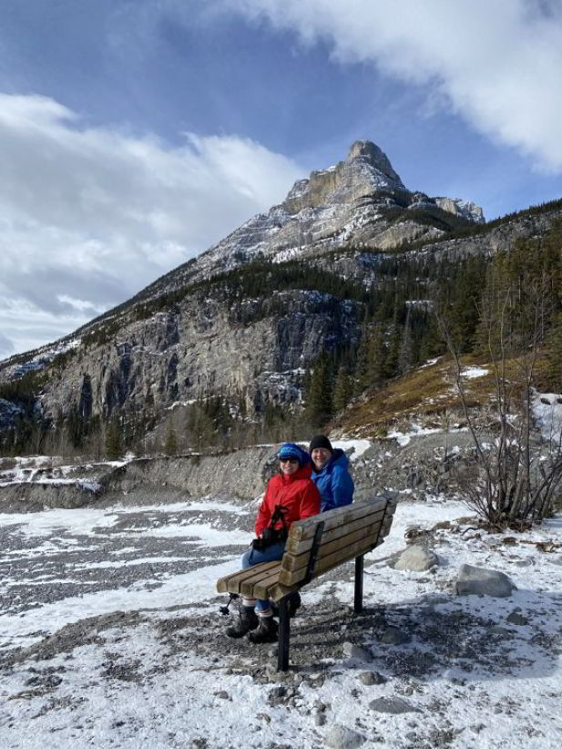 An image of a couple sitting on a bench on the Grotto Canyon hike - best easy hikes in Kananaskis.