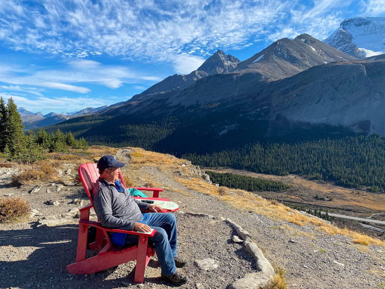 An image of a man sitting in a Parks Canada red chair taking in the view of the Athabasca Glacier as seen from the Wilcox Pass trail on the Icefields Parkway in Jasper National Park in Alberta, Canada.
