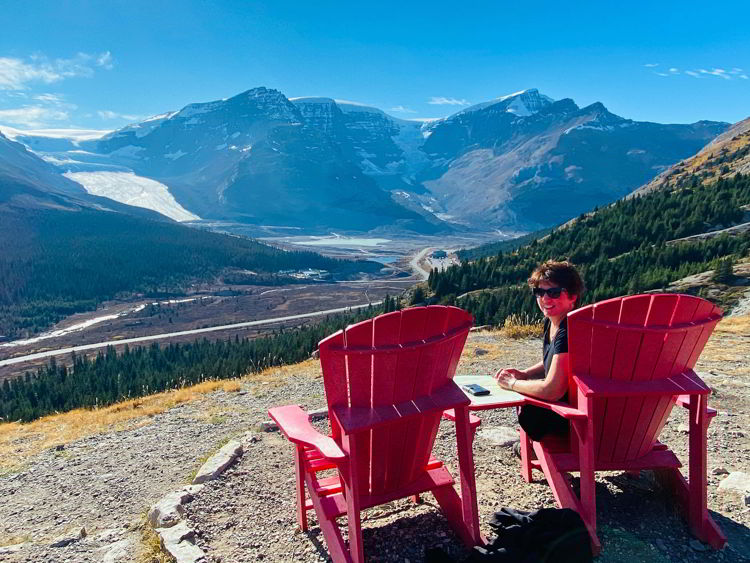 An image of a woman sitting in a Parks Canada red chair taking in the view of the Athabasca Glacier as seen from the Wilcox Pass trail on the Icefields Parkway in Jasper National Park in Alberta, Canada.