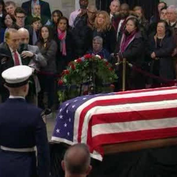 Bob Dole stands to salute casket