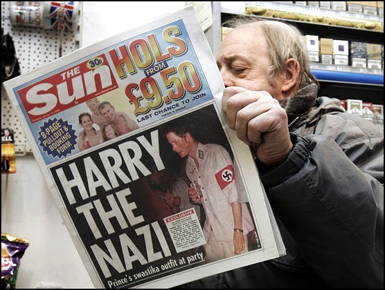 "News agent Roy Ottoway reads a copy of tabloid 'The Sun', whose front page shows a picture of Britain's Prince Harry wearing a Nazi soldier's uniform to a fancy dress party, early Thursday morning, Jan. 13, 2005 at King's Cross station in London. The grandson of Queen Elizabeth II apologized Wednesday night after 'The Sun' printed the picture. Prince Harry, the second son of Prince Charles and the late Princess Diana, was shown in early editions of Thursday's issue of ""The Sun,"" clutching a cigarette and a drink and wearing a swastika armband. (AP Photo/Adam Butler) ** PICTURE MAY ONLY BE USED IN ITS ENTIRETY **"