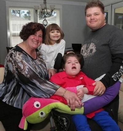 Theresa en Lucas Black met hun dochtertje Angelica in de rolstoel.