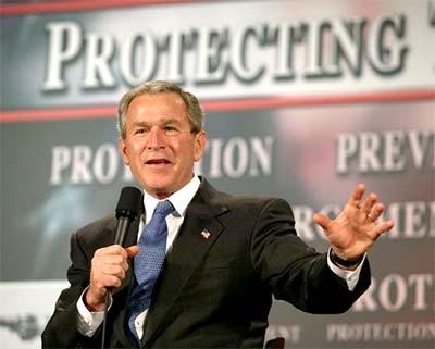 George Bush in zijn rol als beschermende president; achter hem de leus 'Protecting the Homeland'.. Ondertussen zijn de Amerikanen veel van hun fundamentele burgerrechten kwijt; zélf ingeleverd..! Een prachtig motief voor de valse-vlag-aanslagen van 9/11 komt hiermee haarfijn in beeld! De macht uit handen nemen van burgers, die in 'ruil voor bescherming' hun kracht en macht uit handen geven aan JUIST de boeven..