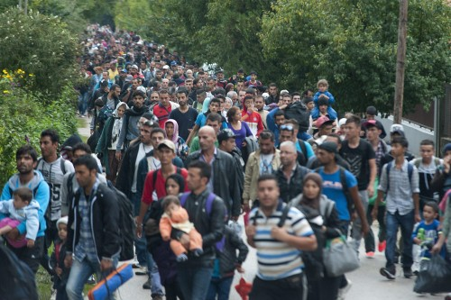 epa04930491 Migrants who had arrived from Roszke by train, walk toward Austria in Hegyeshalom, 168 kilometers west from Budapest, Hungary, 14 September 2015. Thousands of migrants were rushing to reach the EU-member state Hungary before a new law there effectively closes its borders on 15 September. EPA/CSABA KRIZSAN HUNGARY OUT
