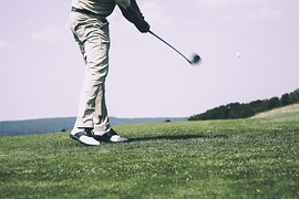 man swinging golf stick