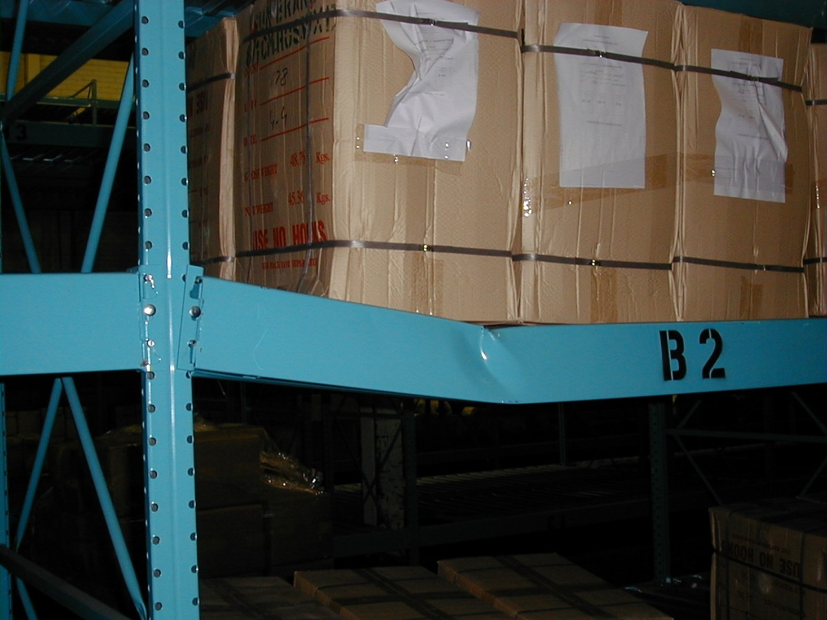 A steel warehouse rack bends under the weight of boxes placed on its shelves.