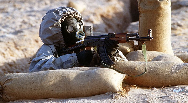 Syria, Syrian soldier in Soviet-made nuclear-biological-chemical warfare suit with AK47, during Op Desert Shield, by HH Deffner (US)