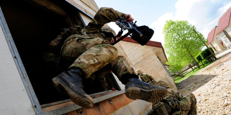 British Army soldier leaps out of a window at the FIBUA (Fighting in a Built Up Area) facility at Copehill Down Training Village (Crown, 2012)