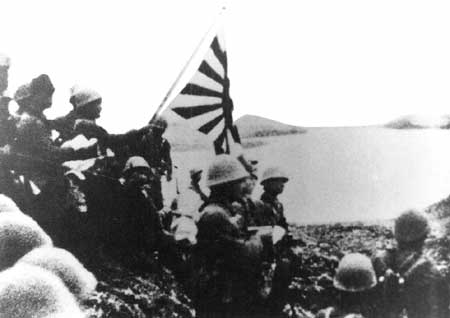 Japanese troops raise the Imperial battle flag on Kiska after landing on 6 June 1942.