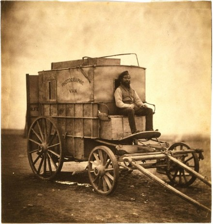 Roger Fenton's assistant sitting on his photographic van.