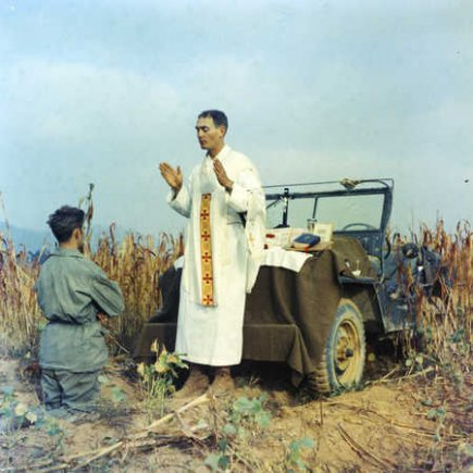 Father Emil Kapaun celebrating Mass using the hood of a jeep as his altar, October 7, 1950.