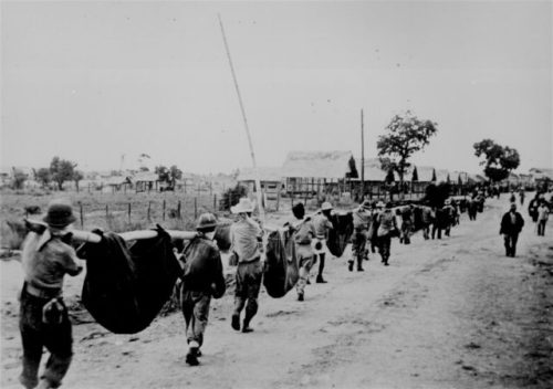 A burial detail of Filipino and prisoners of war uses improvised litters to carry fallen comrades at Camp O'Donnell, Capas, Tarlac, 1942, following the Bataan Death March.