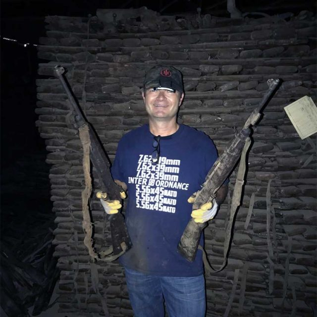 Welgand with two Carbines. Behind him can be seen stacks of more rifles.