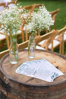 Vases of baby's breath on bourbon barrel with ceremony programs