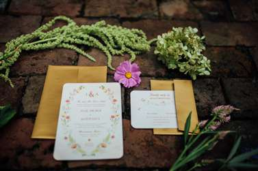 Vintage-inspired wedding invitation and RSVP on bricks with flowers