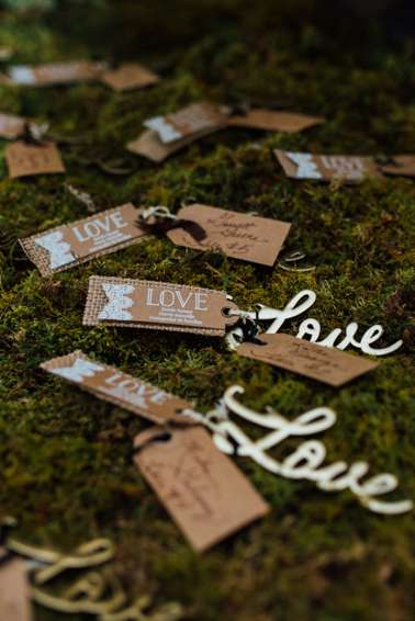 Unique placecards and wedding favors on moss covered table