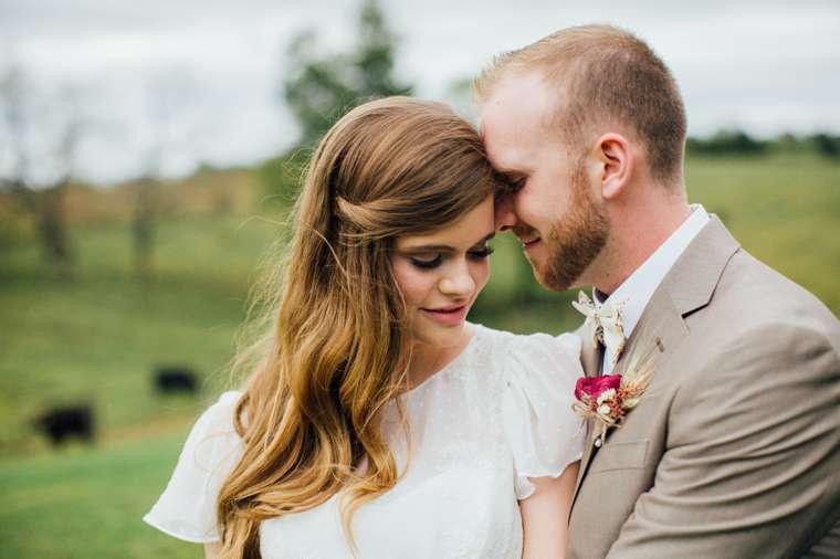 Couple's portrait with farm backdrop