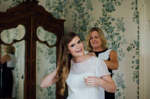 The Mother of the Bride helping the Bride into her dress